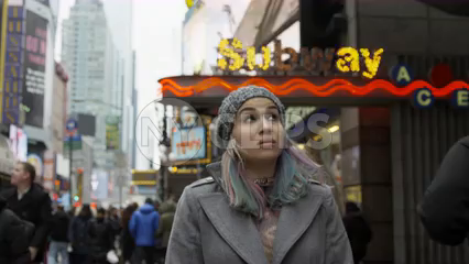 attractive female tourist looking around Times Square signs outside subway station sign - overwhelming bright lights - slow motion 4K NYC