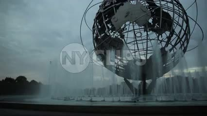 globe sculpture in Flushing Meadows Corona Park Queens NYC - water spraying from fountain in early evening