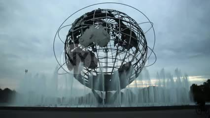 Unisphere globe sculpture with water spraying from fountains in Flushing Meadows Corona Park Queens with kids on bikes