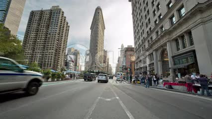 cars and cabs driving down Lower 5th Ave on summer day with Flatiron Building