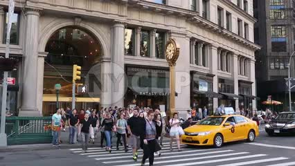 people crossing street at 5th Ave crosswalk with famous clock - man taking picture on summer day