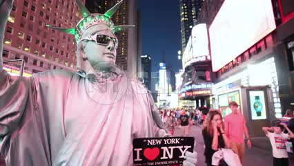 Times Square at night with performer dressed in Statue of Liberty costume