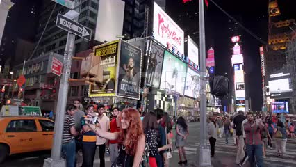 circling around pretty red head girl in Times Square in summer taking selfies at night