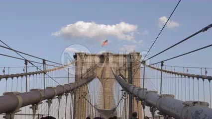 American flag at top of Brooklyn Bridge tower on beautiful blue sky day, people walking below