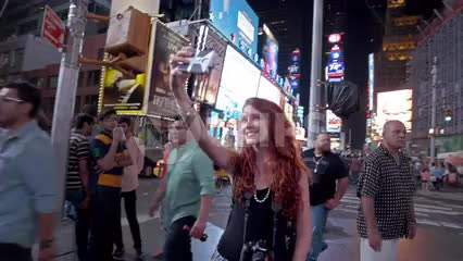 girl recording selfie with smartphone in Times Square on summer night