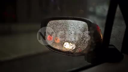 driver's side mirror with raindrops on rainy day - raining in NYC