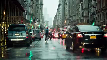 raining on cars in traffic on 5th Ave in early evening in Manhattan NYC