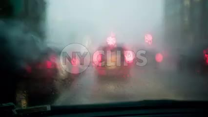 rainy windshield during rain storm from driver pov - driving with wipers wiping away drops on glass - raining with audio
