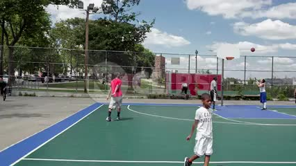 kids playing on basketball courts in New Jersey with view of Manhattan skyline on summer day