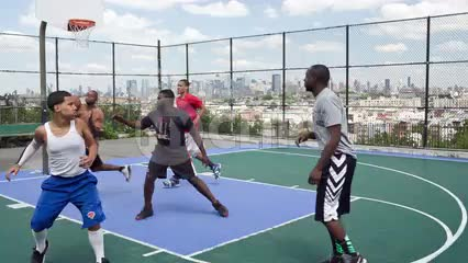 kids in competitive basketball game on outdoor courts with view of Manhattan skyline through fence