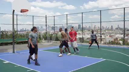 kid scoring alley-oop in basketball on summer day on outdoor court - kids playing with view of Manhattan skyline