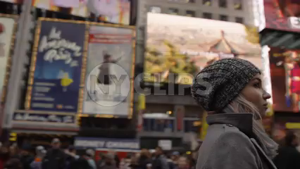 circling lost tourist looking up at overwhelming bright lights and signs in Times Square cold winter - pretty girl with hat in 4K slow motion