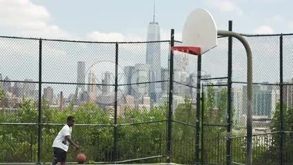 little kid practicing basketball on hot summer day with view of Freedom Tower in NYC through fence
