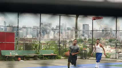 pickup game on New Jersey basketball court with view of Manhattan skyline in NYC with Empire State Building seen through fence