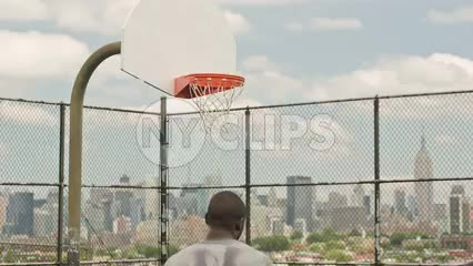 scoring jump shot off backboard on basketball court in summer with Empire State Building view through New Jersey fence