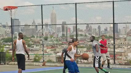 kids playing basketball on summer day with view of Manhattan skyline with Empire State Building in NYC through fence