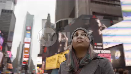 beautiful woman in hat looking up at Times Square signs and ads - bright lights are overwhelming for tourist - 4K slow motion