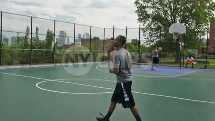 pickup game on summer day with view of Manhattan skyline in NYC through basketball court fence