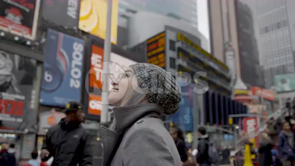 happy tourist looking around in Times Square smiling on cold winter day - pretty girl with hat and ads in 4K slow motion - contact us for model details