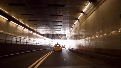 taxi driving in Lincoln tunnel - cab exiting dark into bright white daylight in NYC