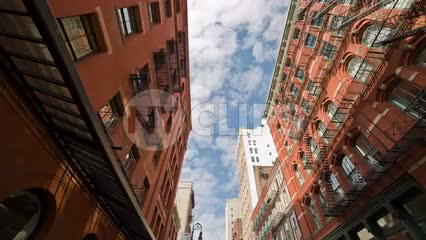 SoHo buildings and cobblestone street in summer - tilting down to cars