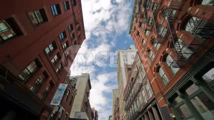 SoHo buildings on summer day tilting down to cobblestone street in NYC