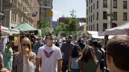 people walking through crowded street fair on hot summer day in NYC