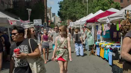 people enjoying beautiful summer day at street fair in New York City