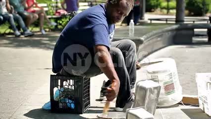 drummer sitting on milk crate in Washington Square Park banging on pots and pans - talented street performer in summer in NYC