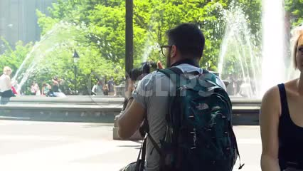 photographer taking pictures in Washington Square Park on summer day - water sprinklers spraying in center - NYC