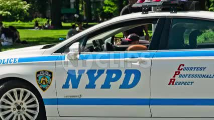 NYPD police car driving through Washington Square Park in summer on bright sunny day - NYC