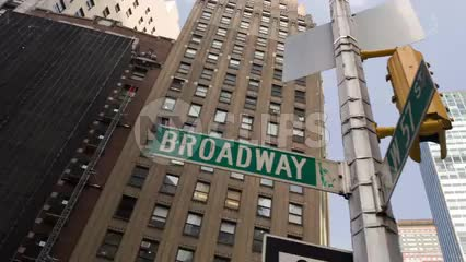 Broadway sign at 57th street panning down to cars in traffic at busy intersection on summer day in Manhattan NYC