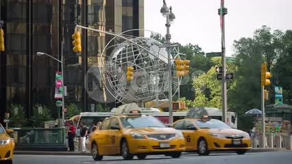 taxi cabs driving in traffic at Columbus Circle with steel globe sculpture on summer day in Manhattan NYC