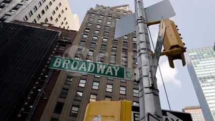 Broadway sign - one way arrow and intersection in Midtown Manhattan with tall skyscraper on summer day