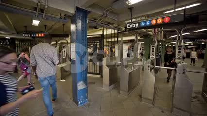 busy subway station in summer - people swiping at turnstiles in NYC
