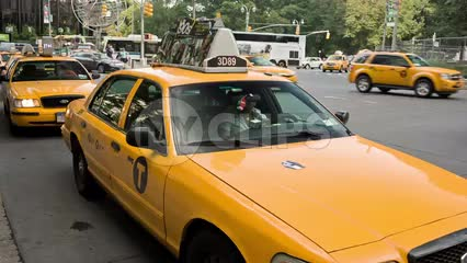 taxi cabs in taxicab stand at Columbus Circle with cars driving by in Manhattan traffic in NYC