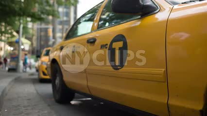woman getting into cab at Columbus Circle - low angle of taxi stand on sunny day in NYC