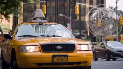 taxi driving off from Columbus Circle on summer day with taxicab stand and steel globe sculpture in background in Manhattan NYC