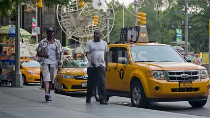 two men walking with Columbus Circle globe statue and taxicabs in background on summer day in Manhattan NYC
