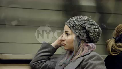 pensive woman riding subway train - sitting with coat and hat in 4K NYC