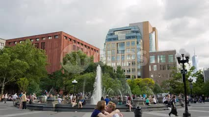 friends hugging in Washington Square Park on summer day with water sprinkler in NYC