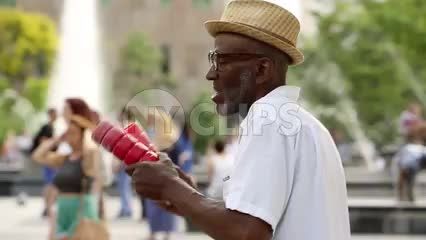 old man playing shakers and singing in Washington Square Park - elderly musician performing in summer in NYC
