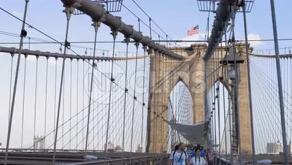 American flag on tower of Brooklyn Bridge on summer day - tourists walking across taking pictures in NYC