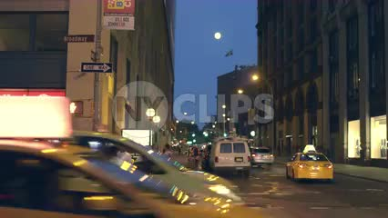 full moon over busy traffic street at night in Manhattan on Broadway in NYC