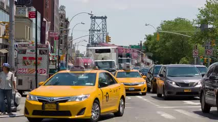 cars and taxi cabs coming off Williamsburg Bridge into Manhattan on summer day in heavy traffic on the Lower East Side in NYC