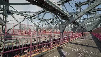 inside view of Williamsburg Bridge with people crossing toward Brooklyn on summer day in NYC