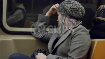 woman in hat sitting in seat riding subway - reflection in window from moving train in 4K NYC