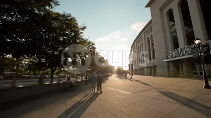 Yankee Stadium exterior at sunset in summer - couple walking by front entrance in the Bronx NYC