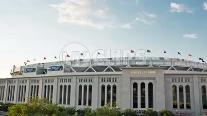 Yankee Stadium with flags on exterior on sunny day in summer - the Bronx NYC