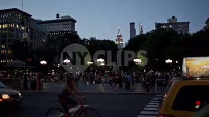 Union Square Park in early evening with Empire State Building lights in Manhattan - summer in NYC